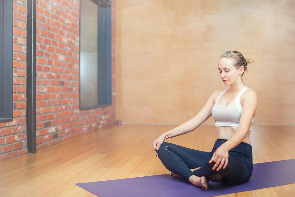 woman sits on yoga mat cross legged
