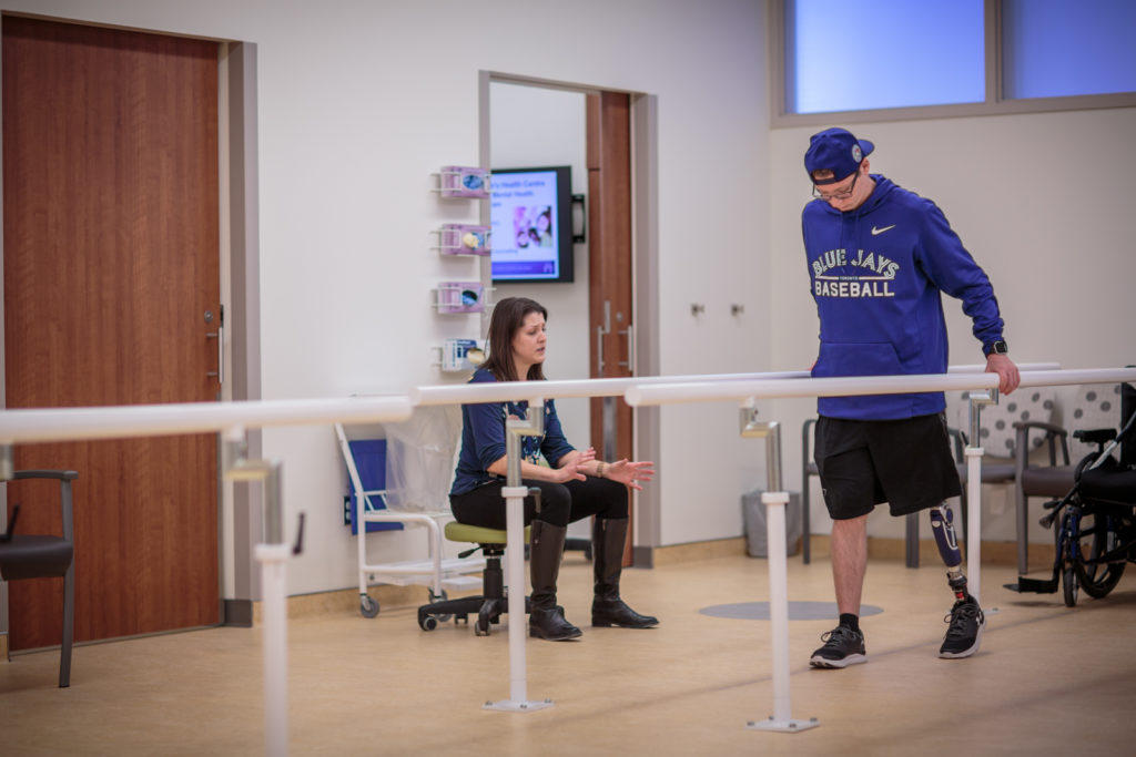 A clinician examines a patient's walking patterns with their prosthetic leg