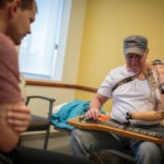 A patient provides feedback on how the guitar piece is progressing and what improvements can be made to help with his specific style of playing.