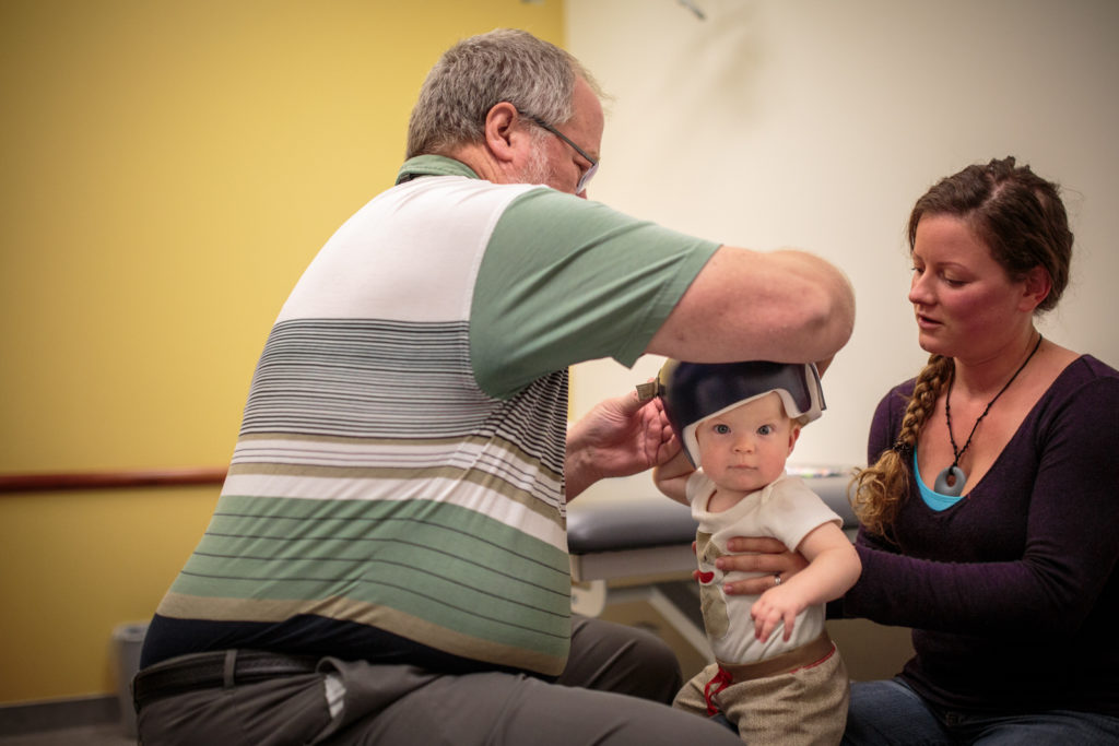 A clinician works with a child to progress with their helmet fitment by making inner liner and adjusting for pressure points.