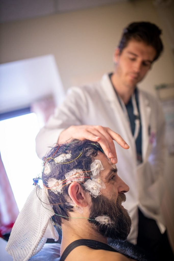 Neurotechnologist checking electrodes on a patients head