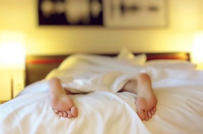 a person is lying face down in bed with their feet poking out from the covers