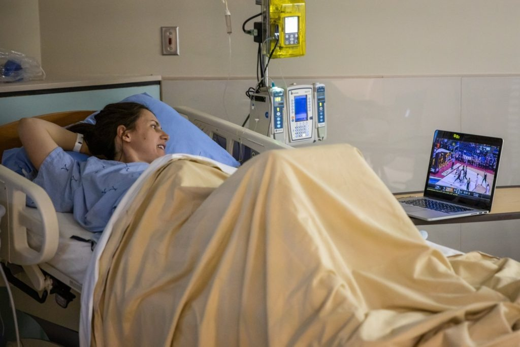 Pregnant woman lays in bed watching sports.