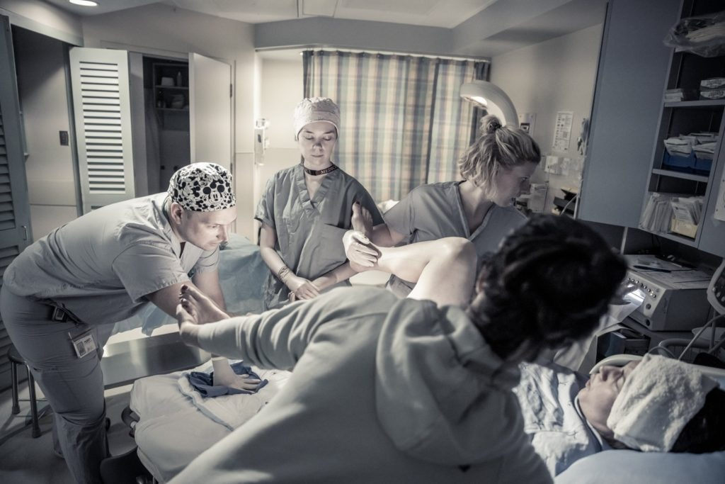 Doctors and nurses are coahing a woman through child birth and went to push.
