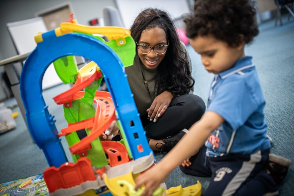 a staff member plays cars with a young boy