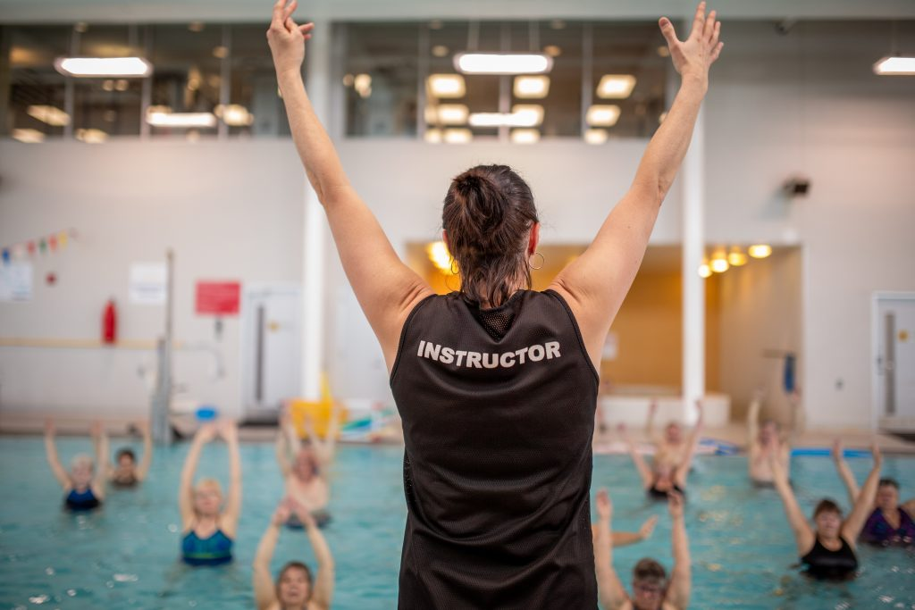 Swimming instructor teaching Annette Attwood's aquatics class