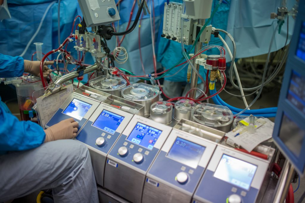 A perfusionist works on a heart lung machine in the operating room