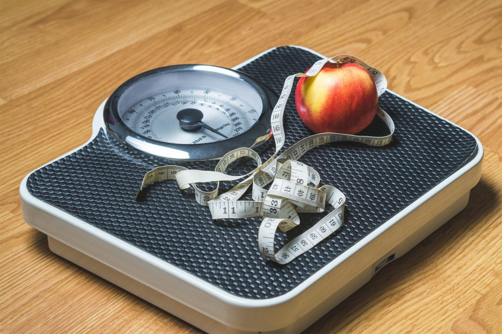 Scale with tape measure and apple implying weight loss