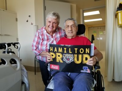 Kathy poses with her husband Bill, holding a Hamilton Proud sign