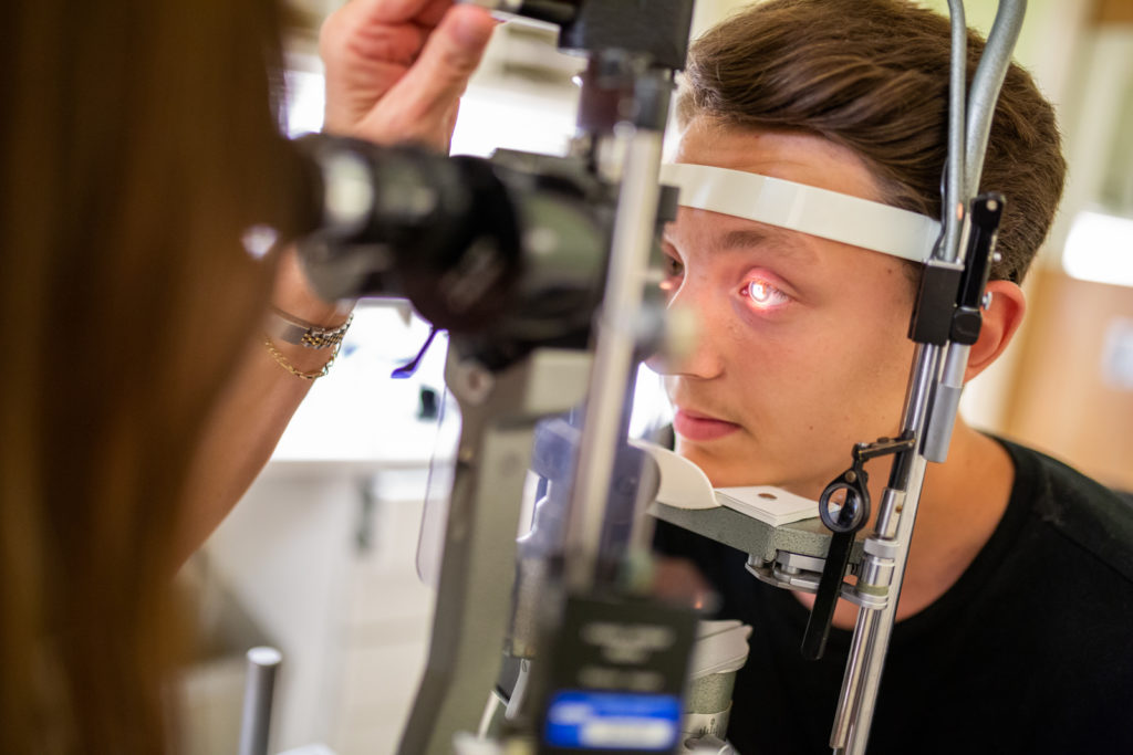 Dr. Isaza looks at Alex's eyes using a special light.