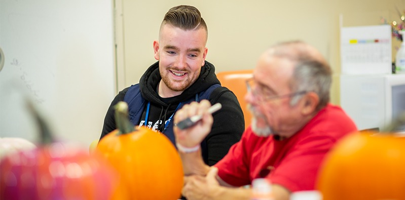 Andrew painting a pumpkin with a patient