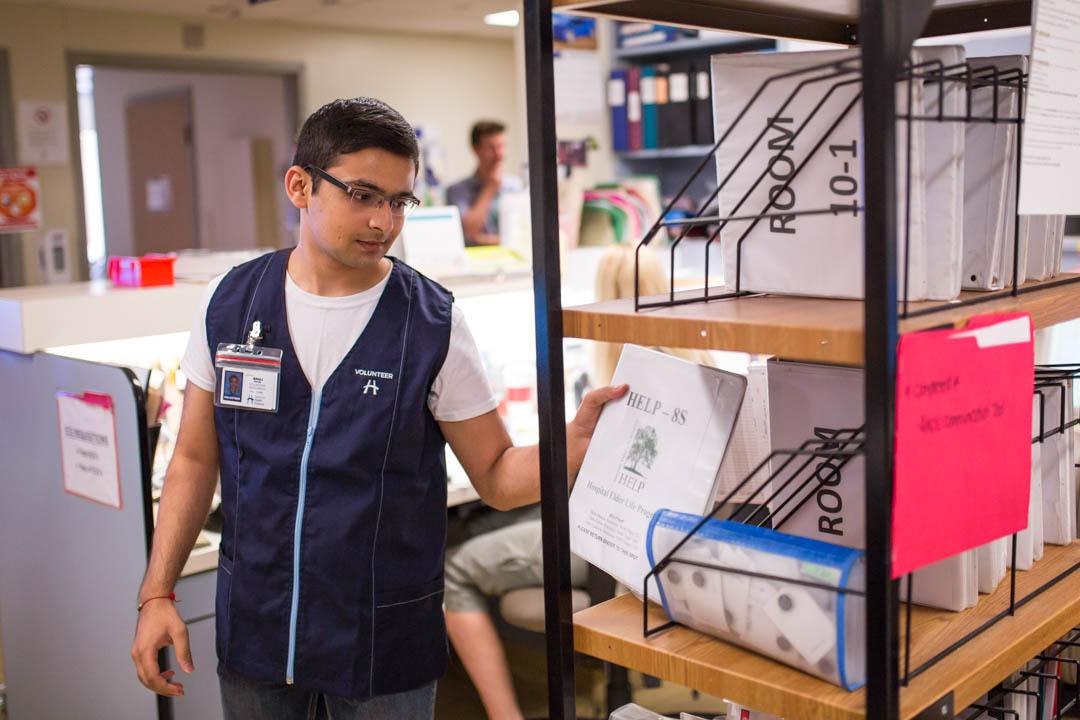 Volunteer Anuj Patel gets his log book from the nursing station