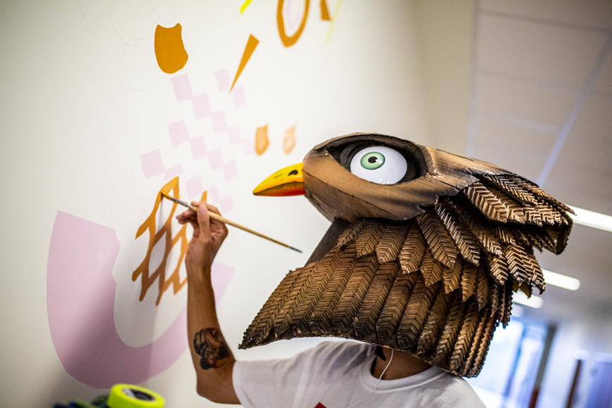 Jerry Rugg, wearing an oversized bird mask that covers his head and neck, paints a white wall pink and yellow