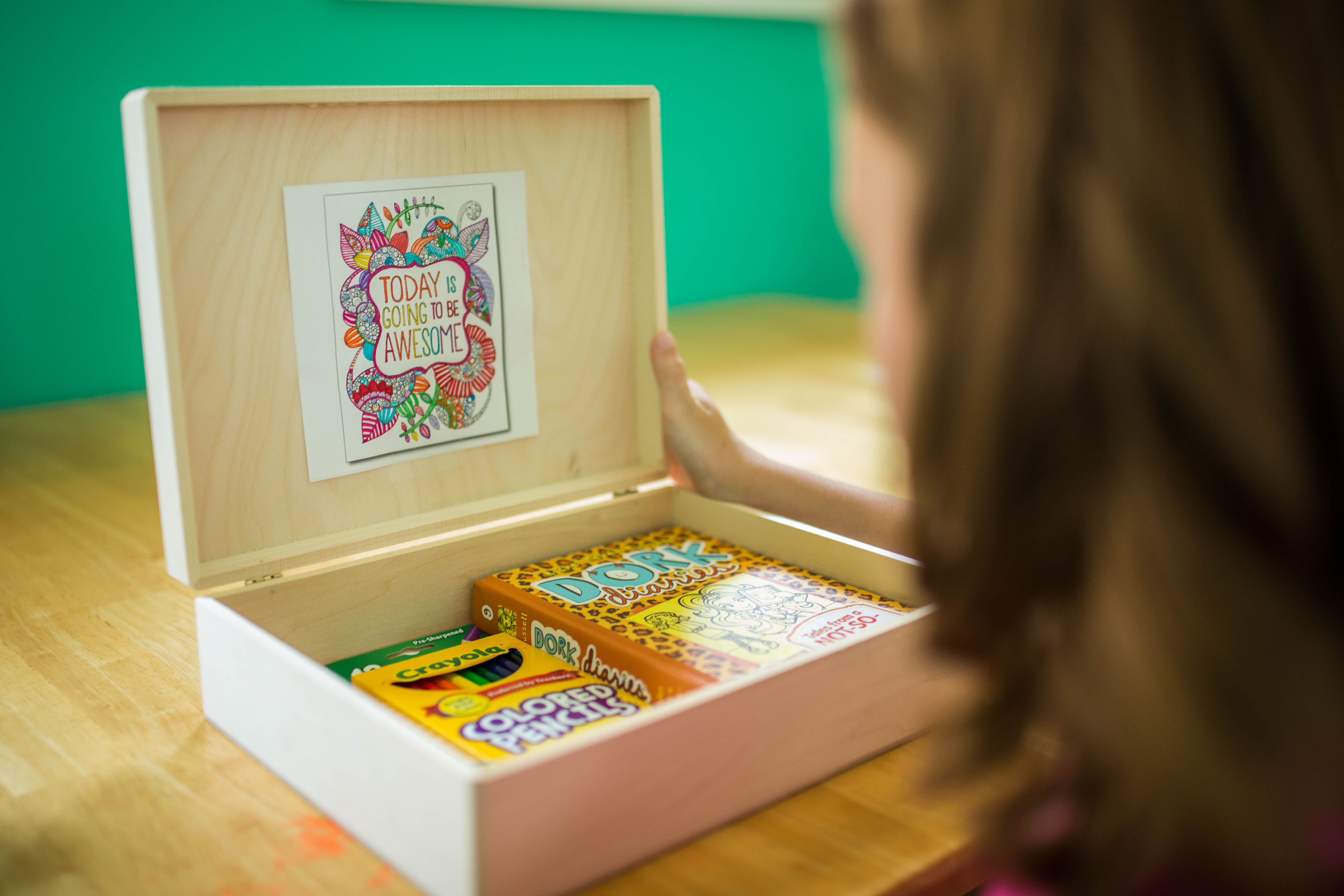 Kayla's coping box contains items like colouring pencils and books