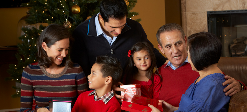 A family gathers around the Christmas tree opening gifts