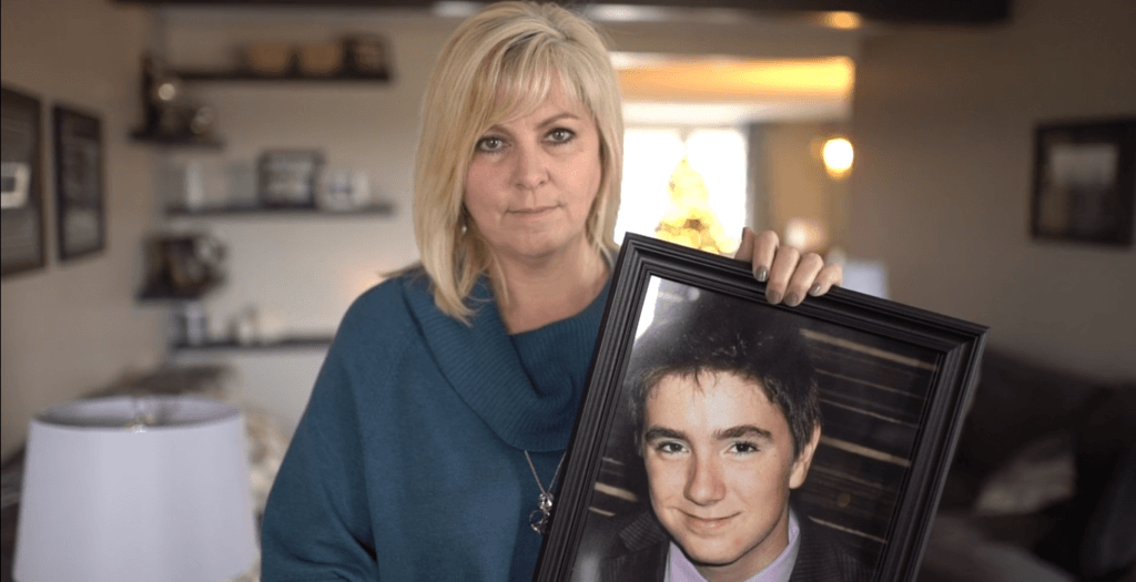 Kim LeBlanc holds up a photograph of her son, Tyler