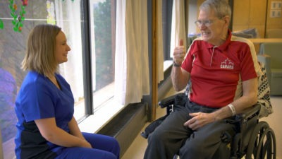Patient in long-term care giving thumbs up to nurse