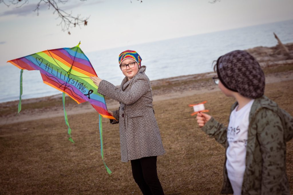 Lilly flies a rainbow kite with her sister, Scarlet