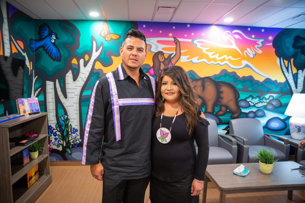 Makayla's parents, Ken and Sonya, stand in front of the mural