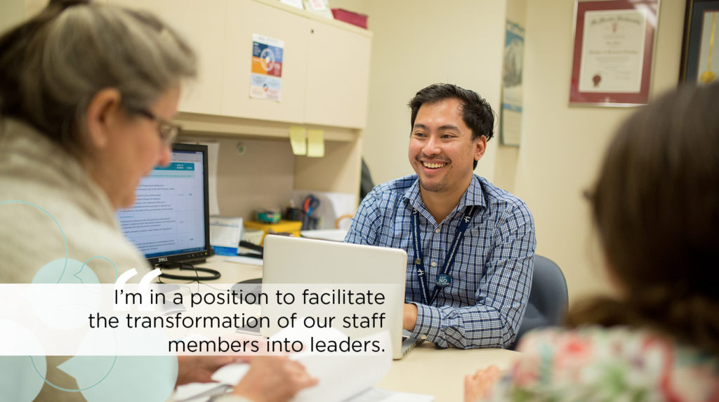 A clinical leader sits at a desk with colleagues in discussion