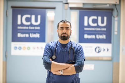 An internationally trained nurse stands in portrait in front of the ICU