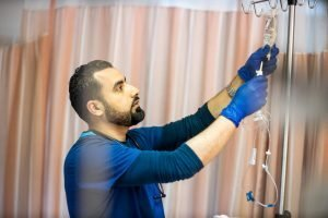 An internationally trained nurse works on an IV