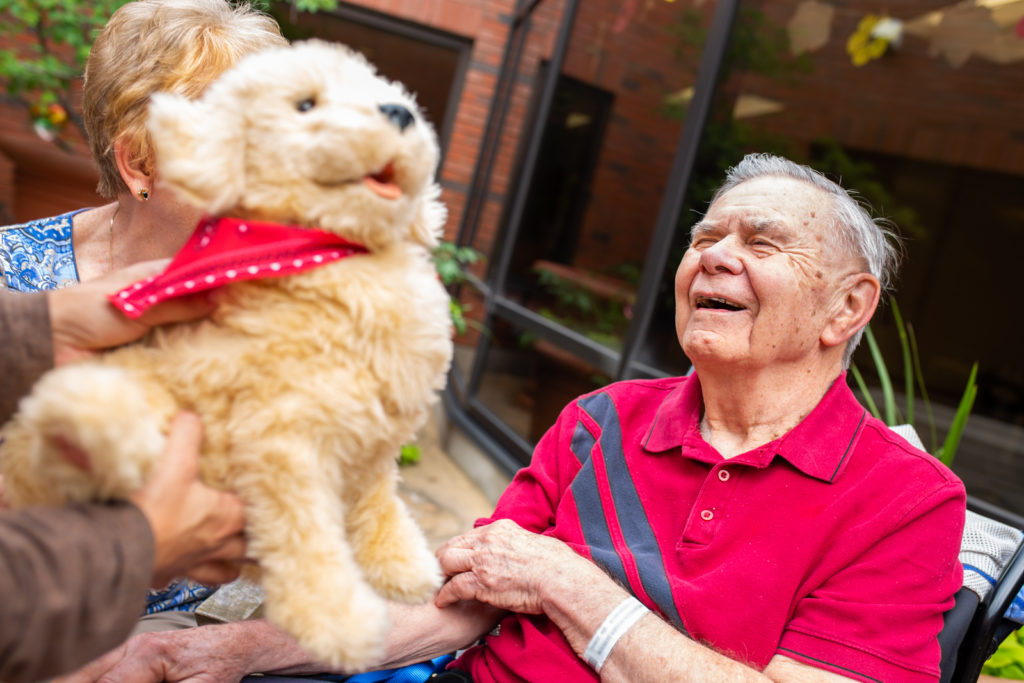 a family member holds up Daisy the robotic dog for patient, Roger, who has dementia