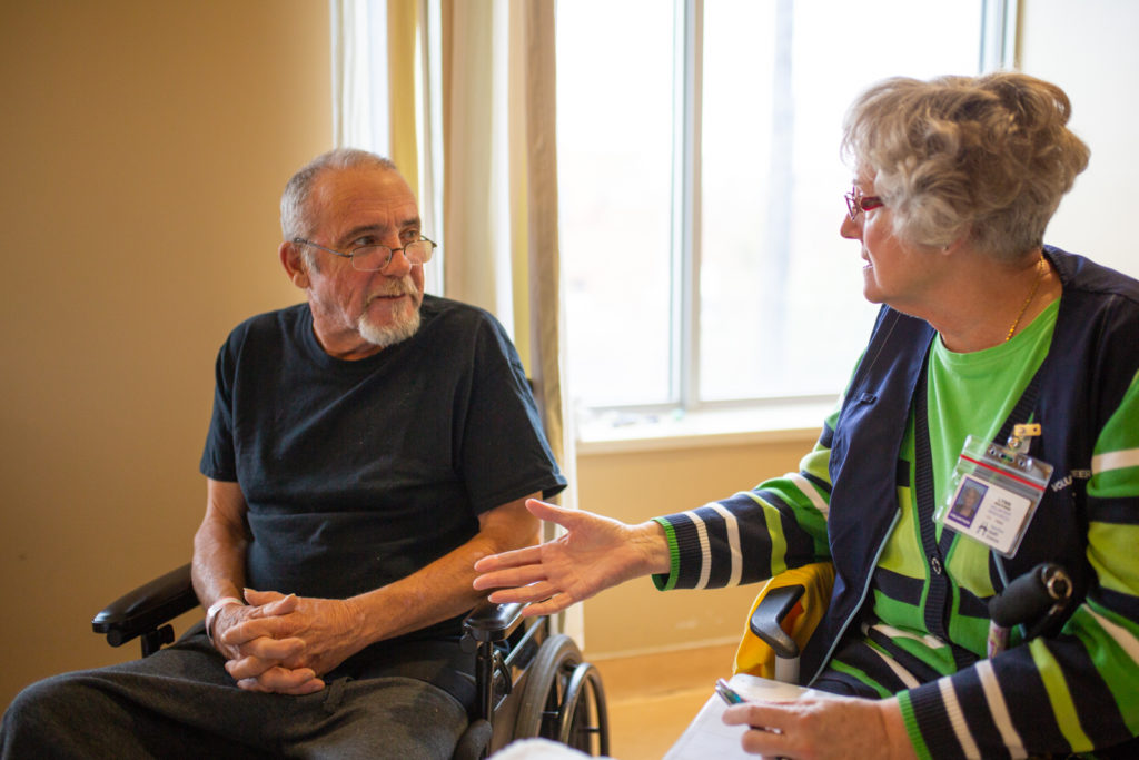 A stroke survivor speaks with a patient in recovery in a hospital room.