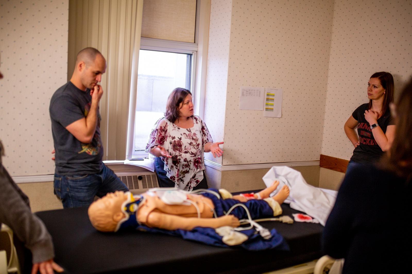 hospital staff gather around a child-size mannequin