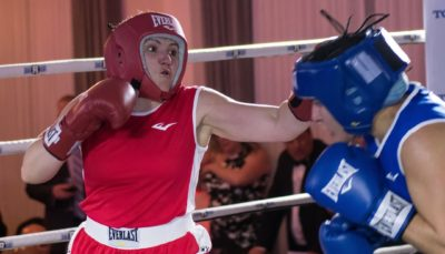 A boxer in red (left) aims for her opponent in blue (right).