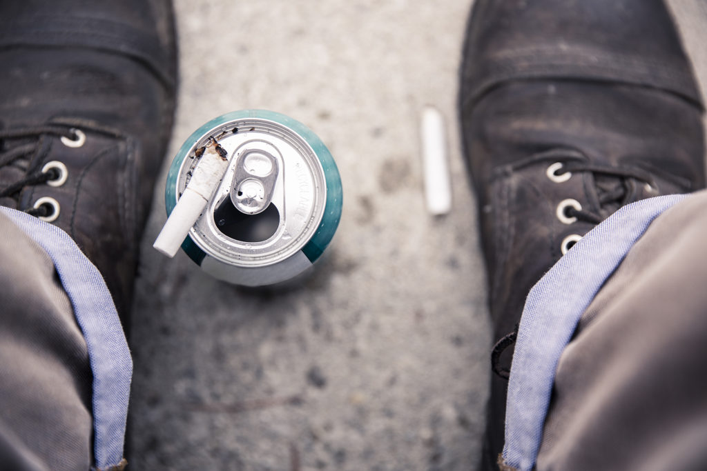 Two male feet surround an empty beer can with a cigarette on top