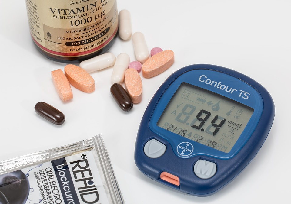 a blood sugar monitor and a bottle of vitamins