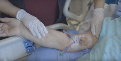 Close up of a nurse checking a central line in a patient's arm