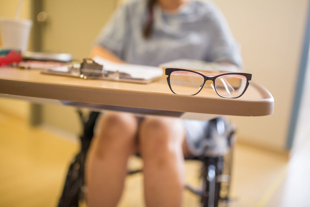 a pair of glasses sit on a patients bedside table