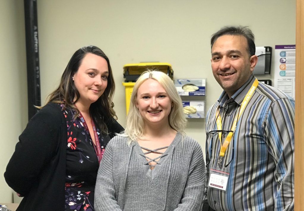 Nurse Ashley Fournier, patient Katie McMurrough and Dr. Ahmed Attar pose together in an exam room