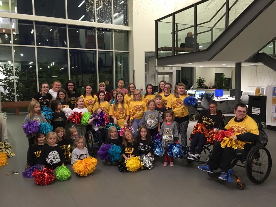 The cheer squad poses for a group photo with their pom poms
