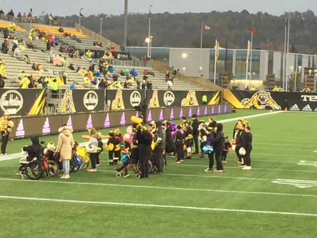 the squad cheering on the football field in the rain at Tim Horton's Field