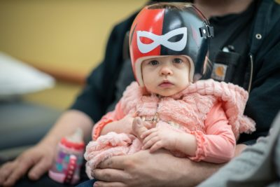 A baby wearing a black and red helmet