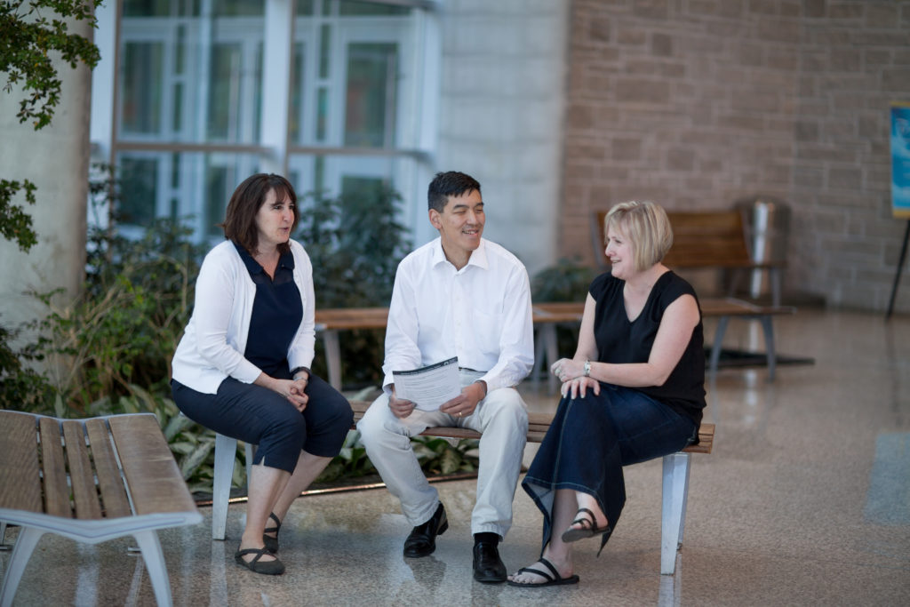 patient advisor, Martha Winhall, Dr. John You, and Marilyn Swinton sit on a bench talking in a brightly lit atrium