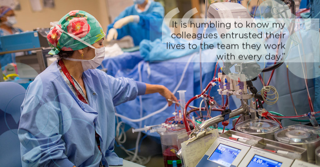 Perfusionist works in operating room setting up heart lung machine
