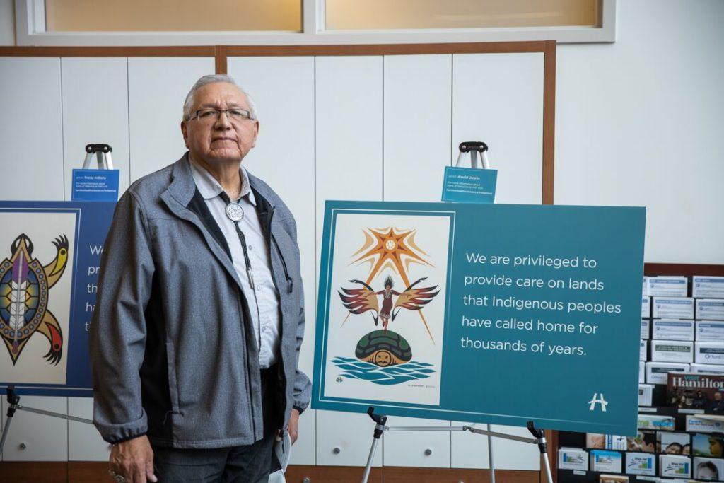 Artist, Arnold Jacobs, standing with his sign of welcome poster