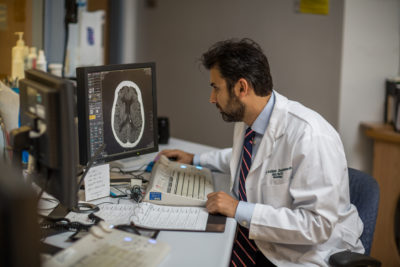 researcher analyzing a brain scan after a stroke