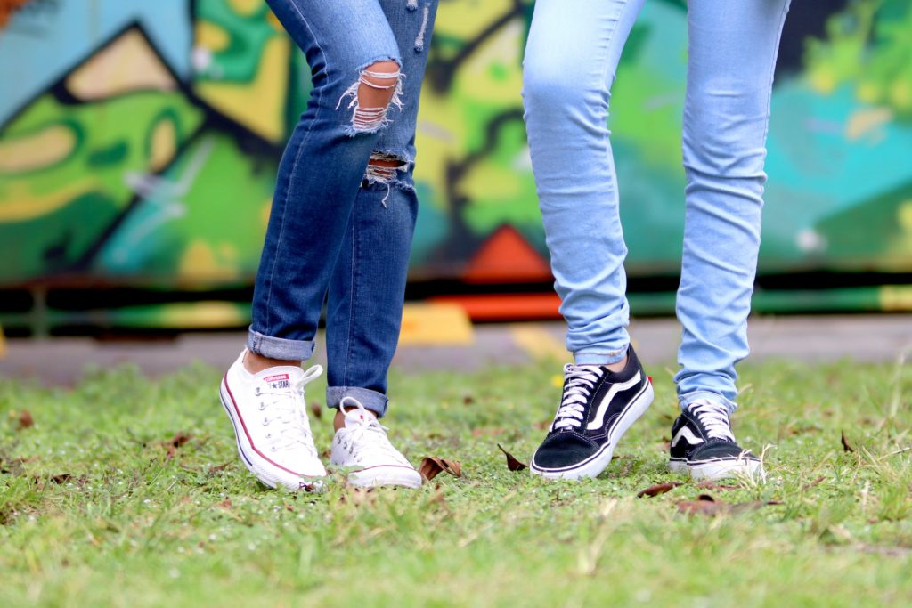 The legs of two teenage girls in jeans and sneakers, standing on grass