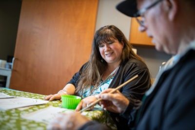 A recreation therapist helps a patient with painting in an art group.