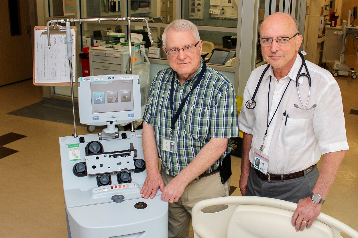 Dr. Brian Leber and Dr. Irwin Walker pose for a photo next to an apheresis machine.