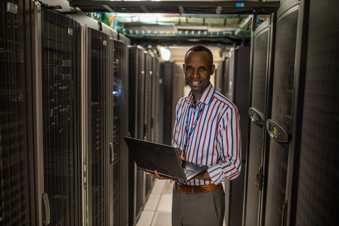 A System Administrator stands in portrait in a server room
