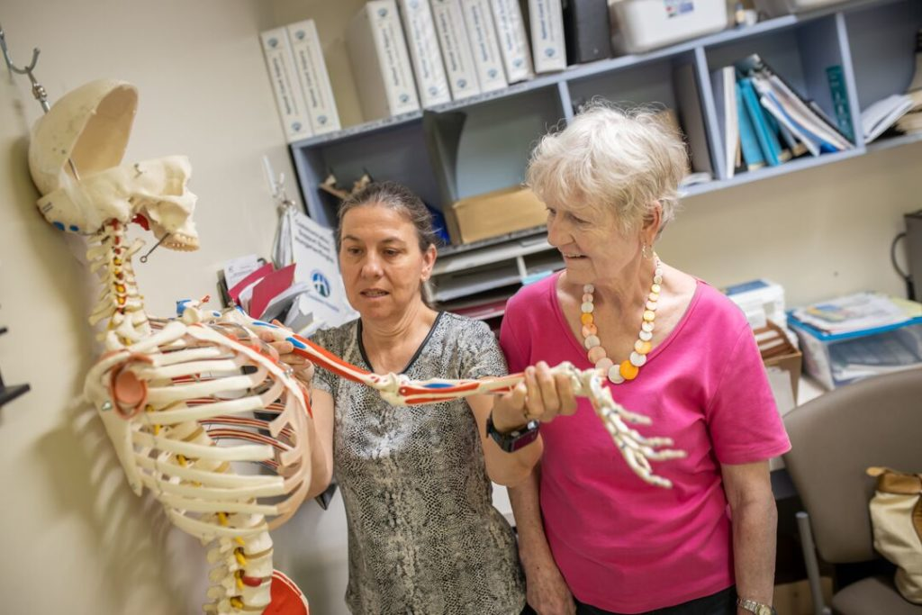 Esther McEvoy shows patient, Sandra Gmell, the shoulder joint on a skeleton