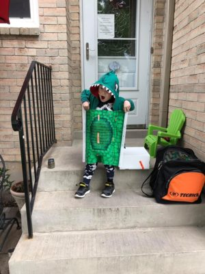 Charlie is dressed in his dinosaur cast outside his home