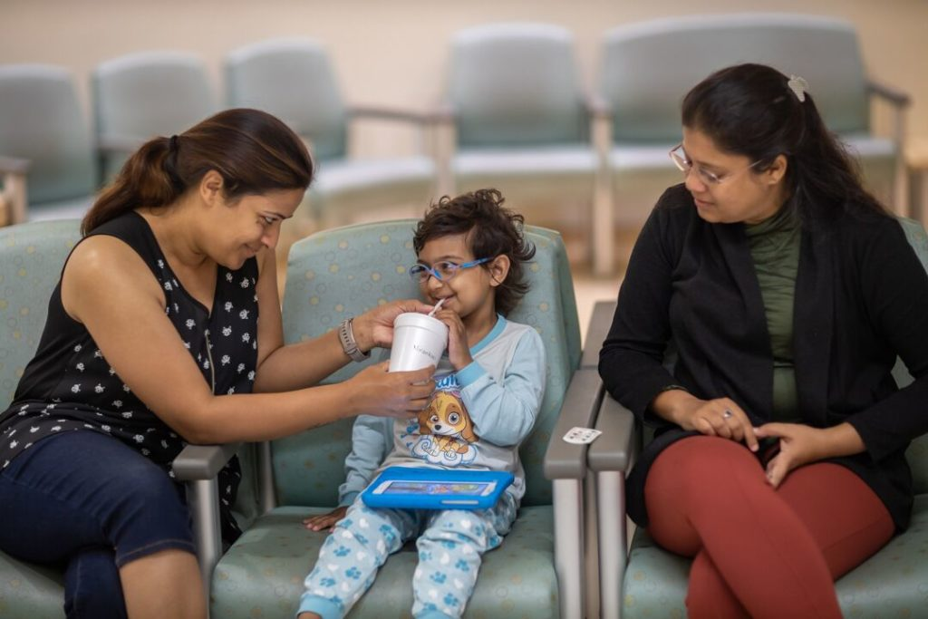 Sophie's mom and aunt encourage her to drink her oral contrast beverage, which will help create a clear picture of her insides during the CT scan.