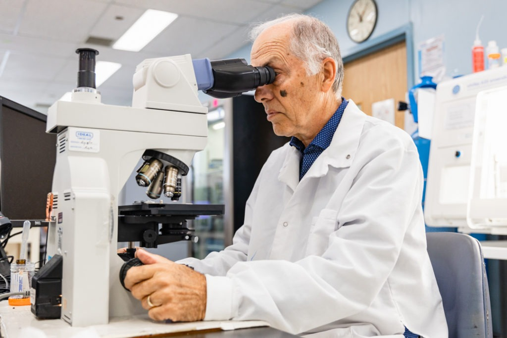 John Korver looks through a microscope